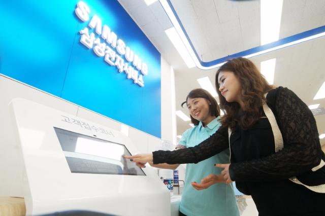 삼성전자서비스를 방문한 고객이 직원의 안내를 받고 있다.