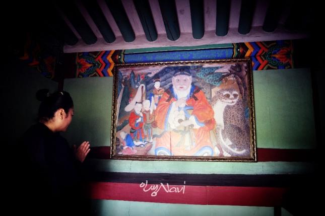 한 무속인이 남양주 덕릉마을 산신각(德陵─山神閣)에서 기도를 올리고 있다.