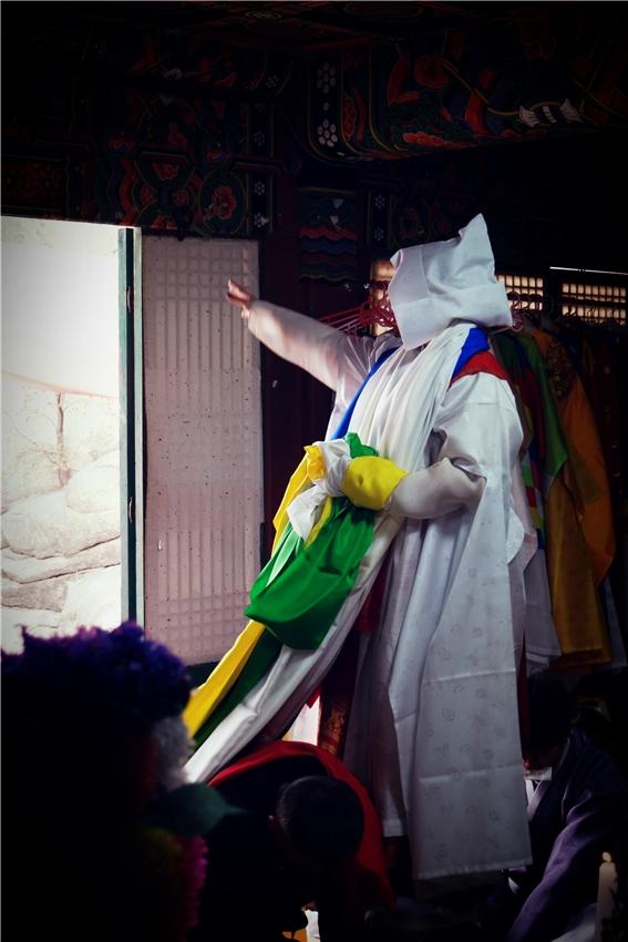 서울특별시 무형문화재 제35호 이수자 무당 김금휘씨가 물동이에 올라가서 물동이 위에서 공수를 주고 있다.