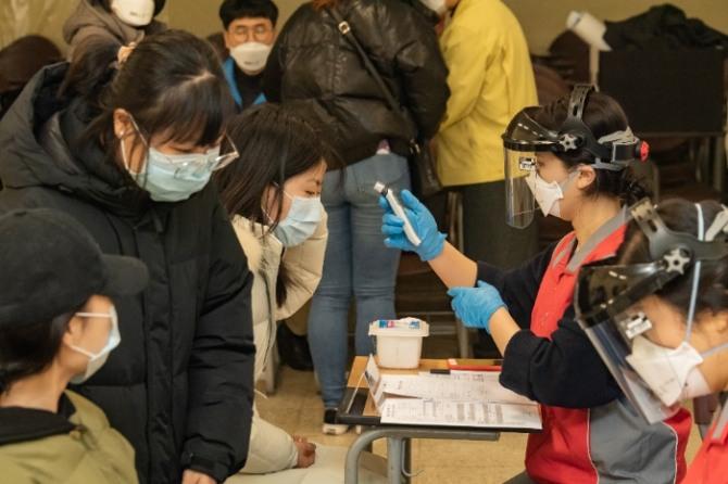 귀국 유학생들이 지난 12일 서울 세종대학교 광개토관에 마련된 임시 선별진료소에서 신종 코로나 바이러스 감염증(COVID-19) 2차 검진을 받기 전 체온을 측정하고 있다. 사진=뉴시스